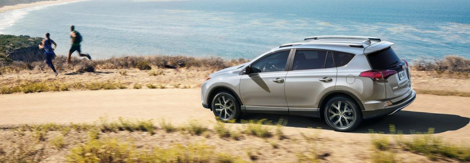 The 2018 Toyota RAV4 driving down a road by the beach and ocean.