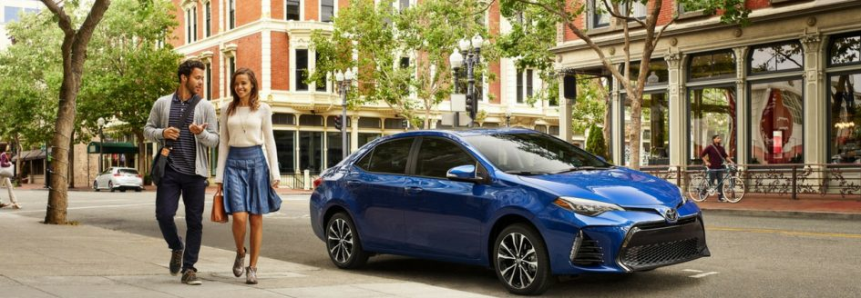 2019 Toyota Corolla parked curbside as two people walk past