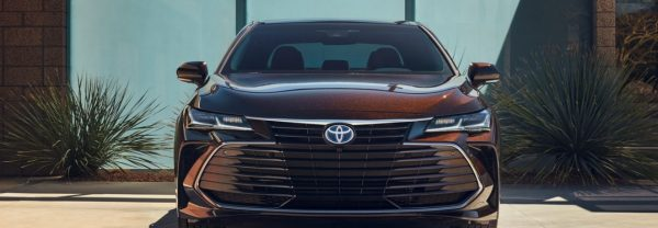 New 2019 Toyota Avalon in opulent amber parked in front of a modern home