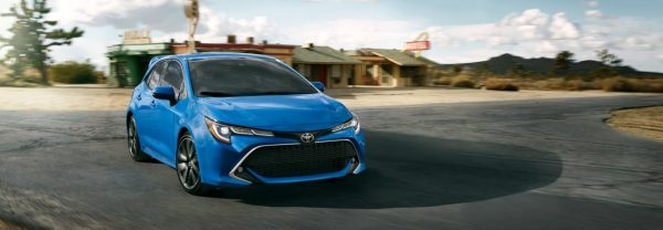 2019 Toyota Corolla Hatchback in blue rounding a paved corner along a desert road.